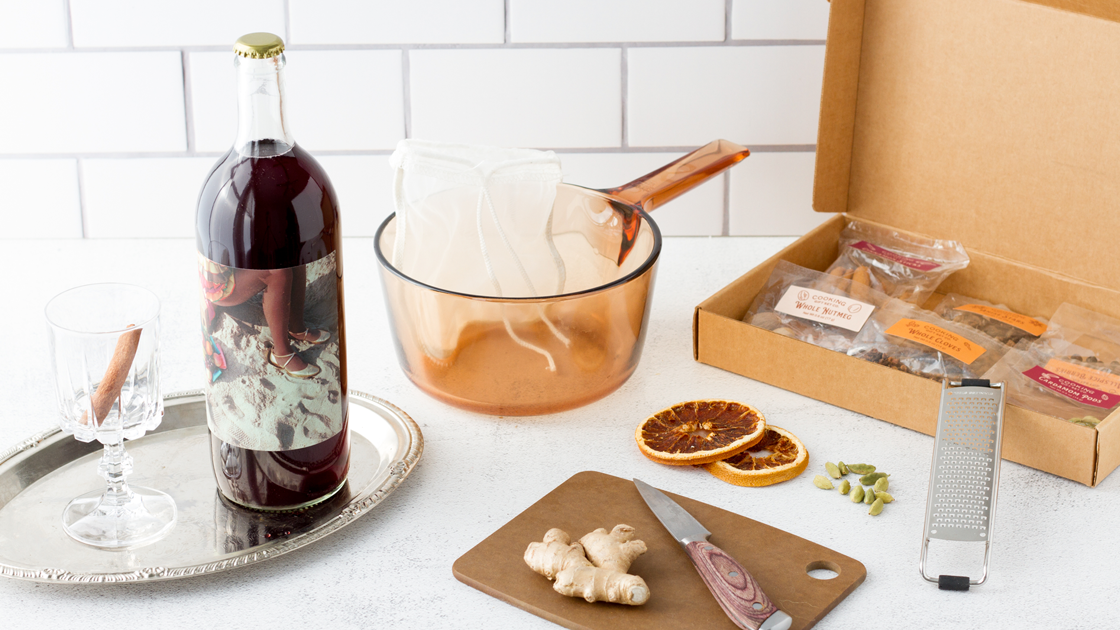 A bottle of Sangia red blend wine and a Mulled Wine kit on a white counter.