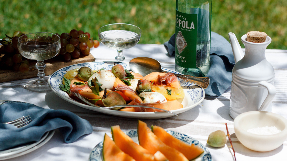 An outdoor table set with a plate of melon, white wine and a burrata salad.