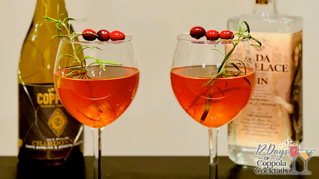 Two Cocktails garnished with cranberries and a bottle of gin and chardonnay in the background.