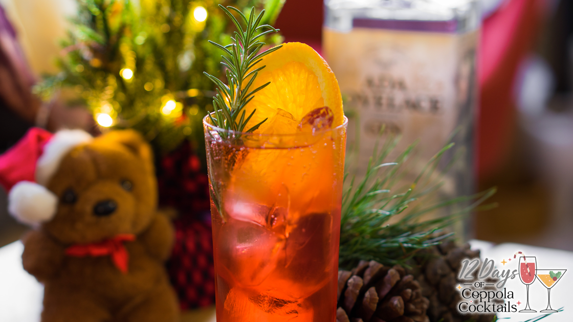 Christmas decoration surrounding a cocktail and bottle of gin.