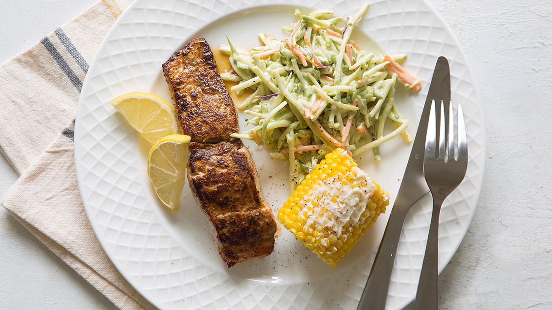 Blackened Mahi fillet with corn on the cob, slaw and lemon wedges.