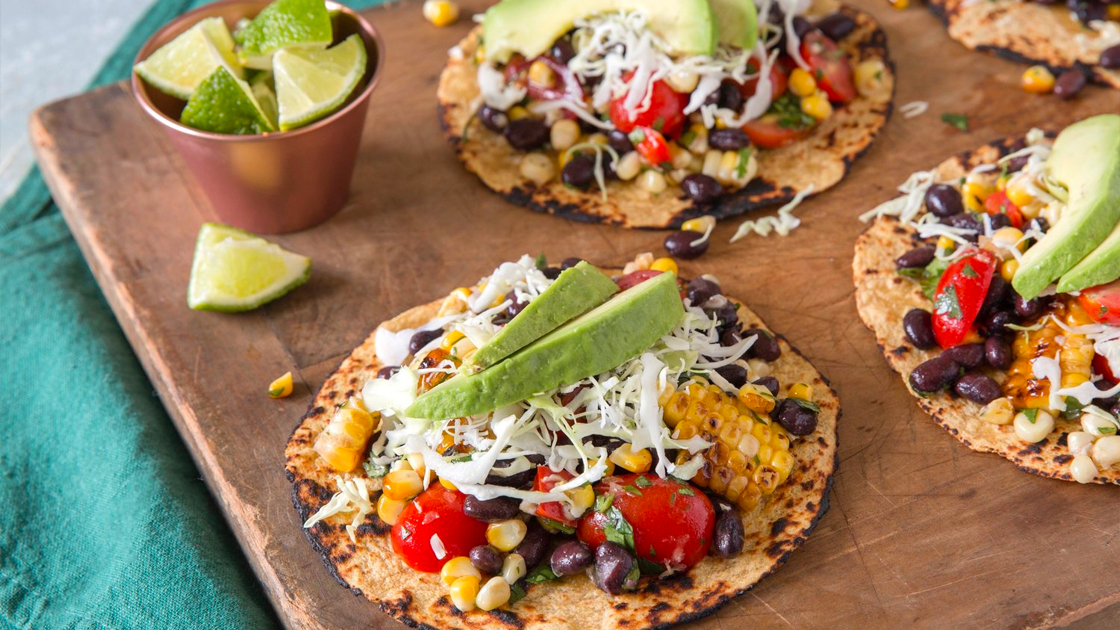 Black Bean and Corn Grilled Tostadas topped with avocado and lime wedges on the side.