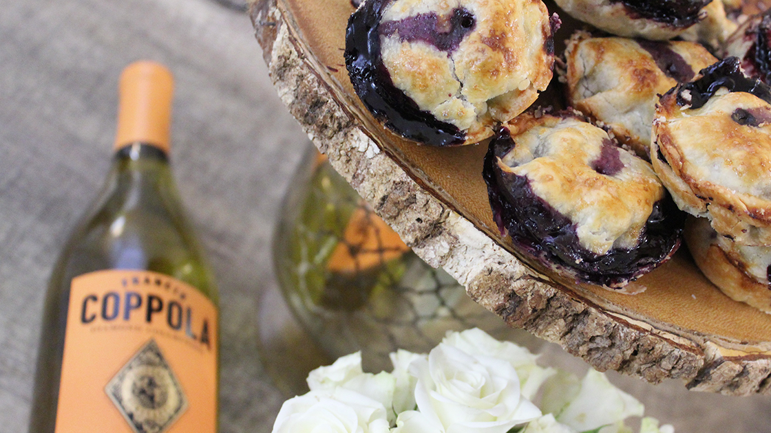Blueberry hand pies in a stack and a bottle of Diamond Collection Chardonnay.