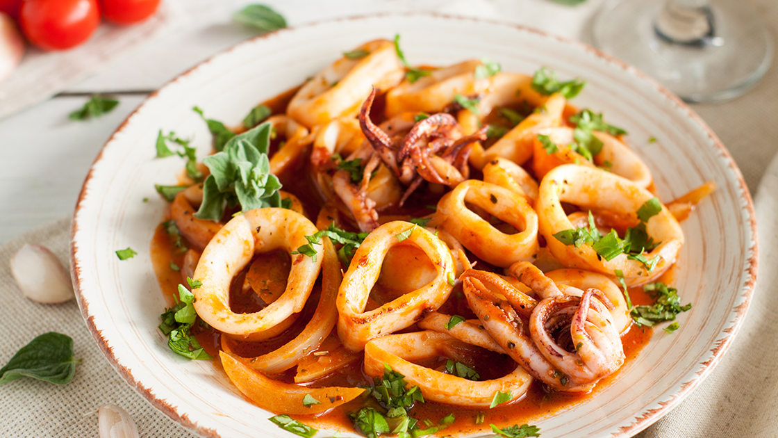 A bowl of calamari in a red sauce.