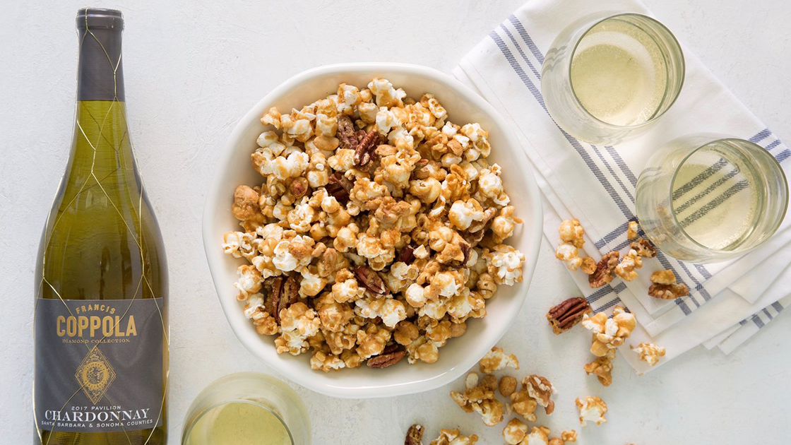 Large bowl of caramel corn with a bottle of chardonnay and three glasses.