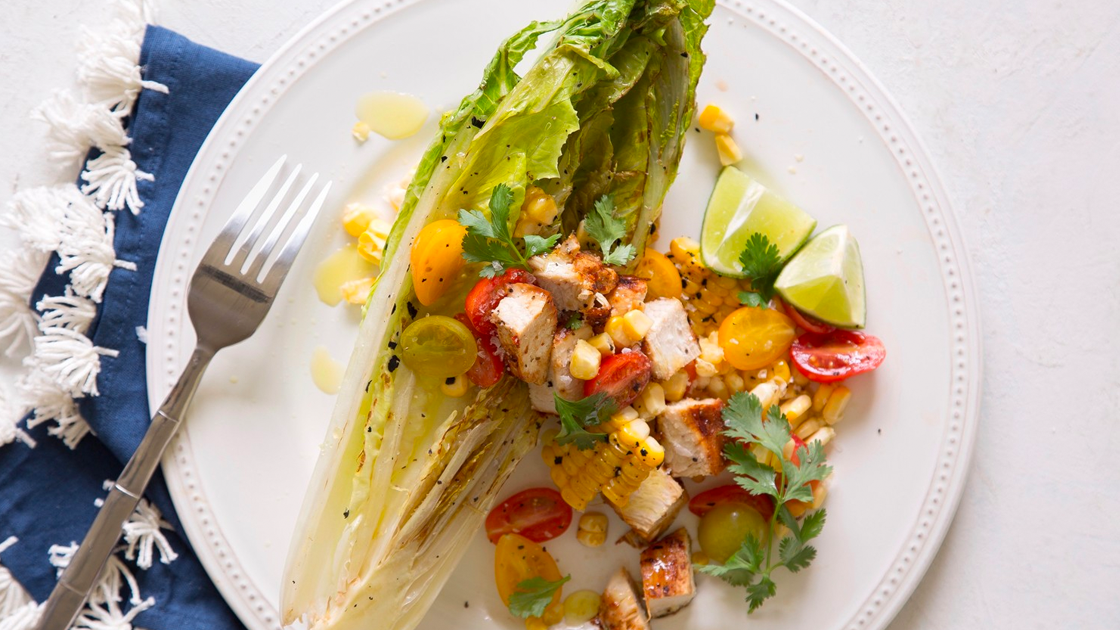 Salad topped with chicken, tomatoes, corn and lime.