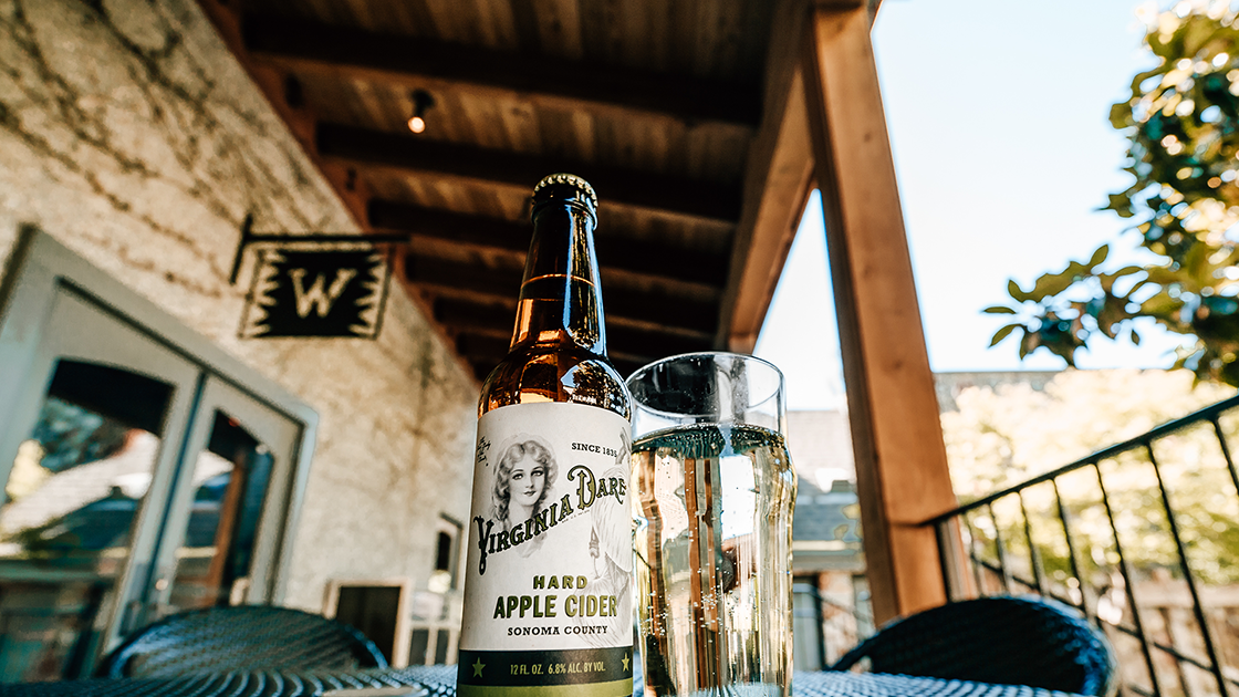 Bottle of Virginia Dare Hard Apple Cider and a glass on a sunny patio.