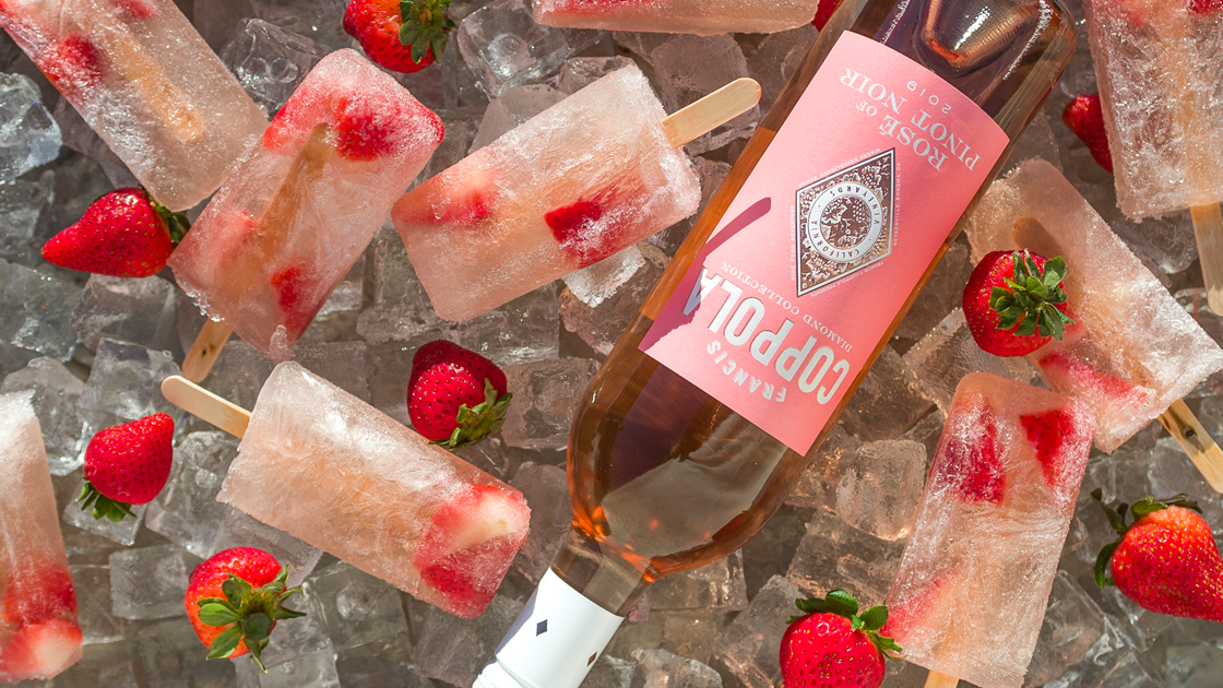 Bottle of Rosé on ice surrounded by strawberries and popsicles.
