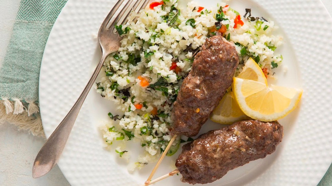 Two Greek beef skewers on a plate with lemon wedges, a fork and cauliflower tabbouleh.