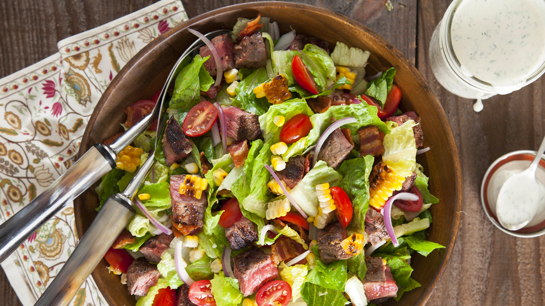 A large salad topped with cubed steak, tomatoes, corn and onion in a wooden bowl next to jars of ranch dressing.