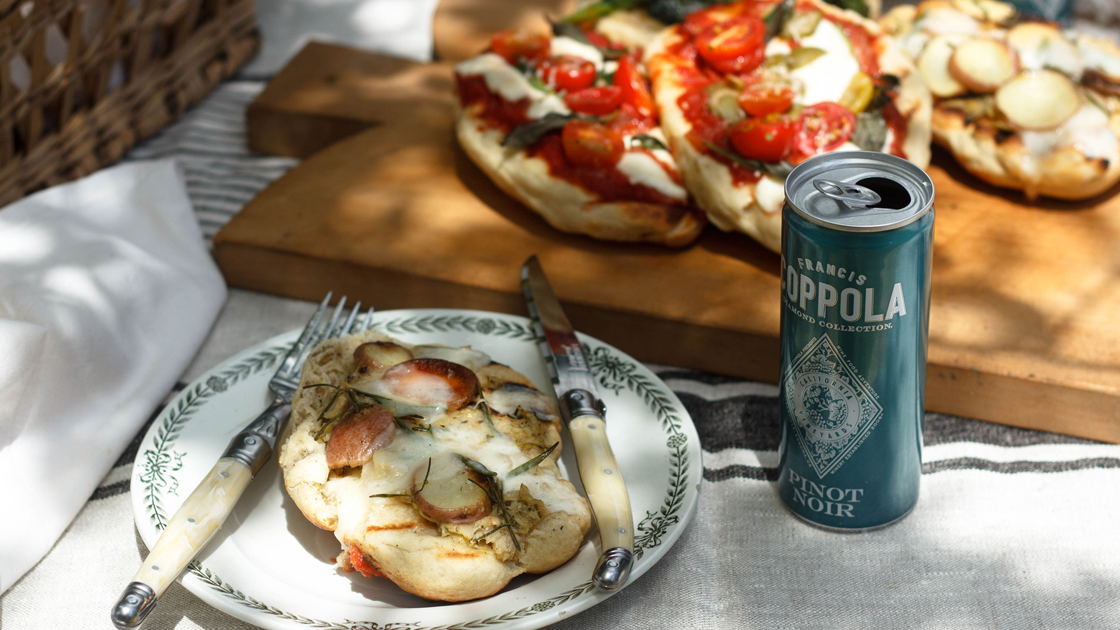 A grilled pizza on a plate with a knife and fork, next to a can of pinot noir.