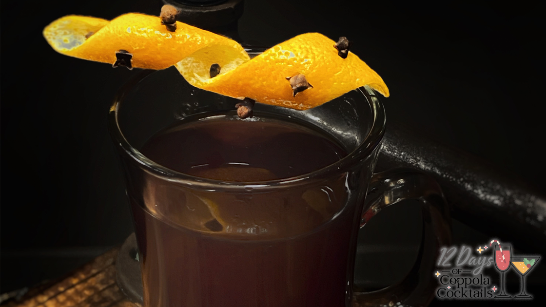 A Hot Toddy cocktail with a clove orange peel garnish.