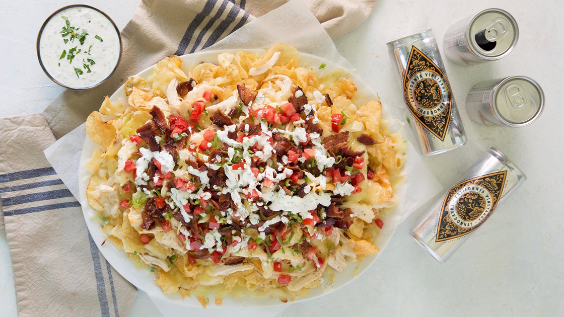 Plate full of nachos made with kettle chips, a bowl of ranch dressing and cans of Diamond wines.