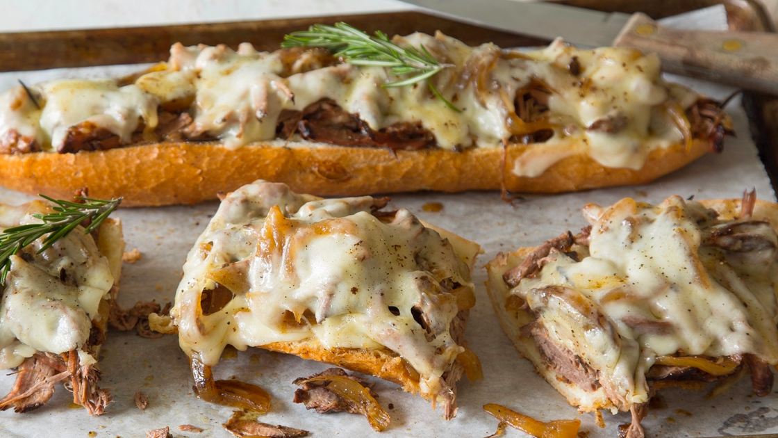 Baguette covered with shredded lamb and melted cheese, garnished with rosemary.