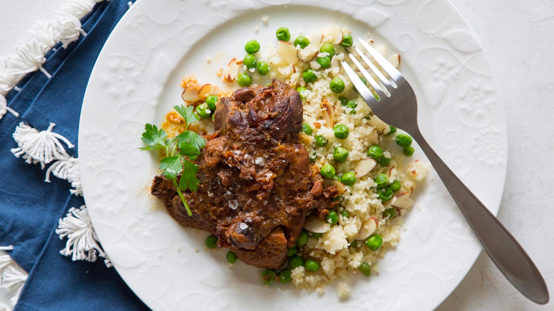 Spiced chicken with couscous and peas on a white plate on top of a blue napkin with tassels.
