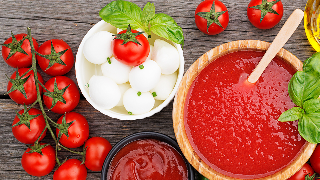 Tomatoes on a vine next to a bowl of mozzarella and a bowl of tomato sauce.