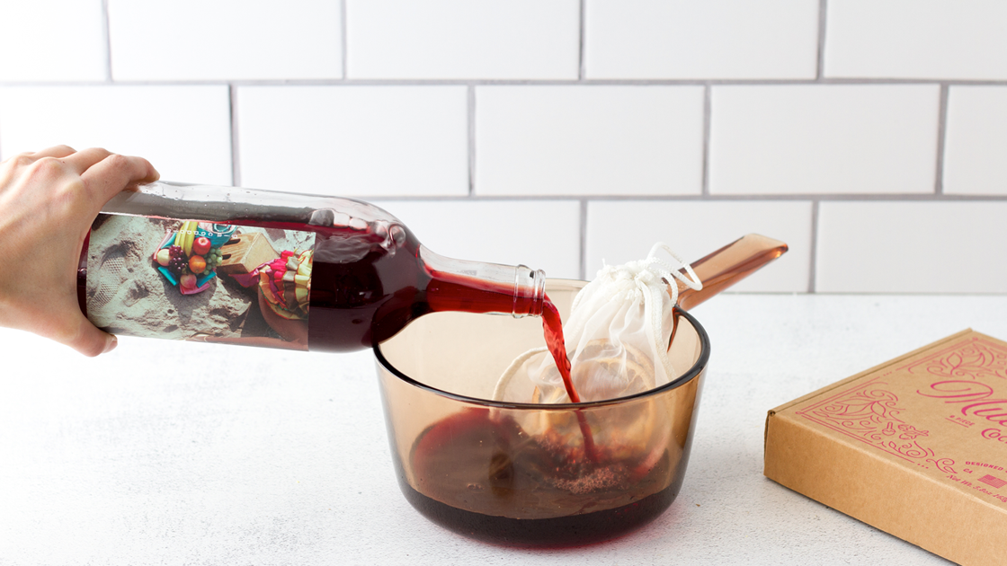 Red wine being pour into a pot with a Mulled wine kit.