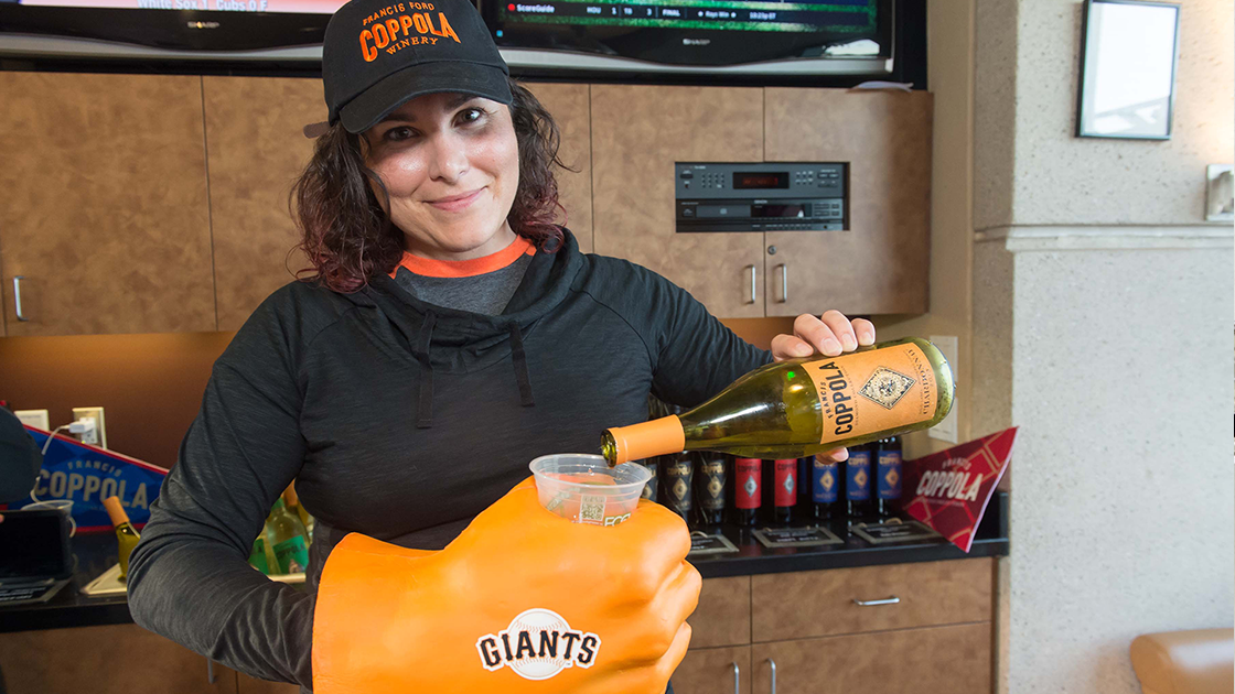 Natalie Dale in a baseball hat pouring Diamond Chardonnay into a cup held by a giant orange foam fist.