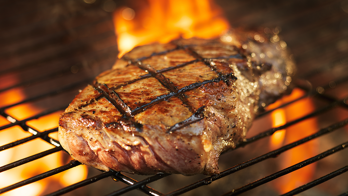 Steak on a flame grill.