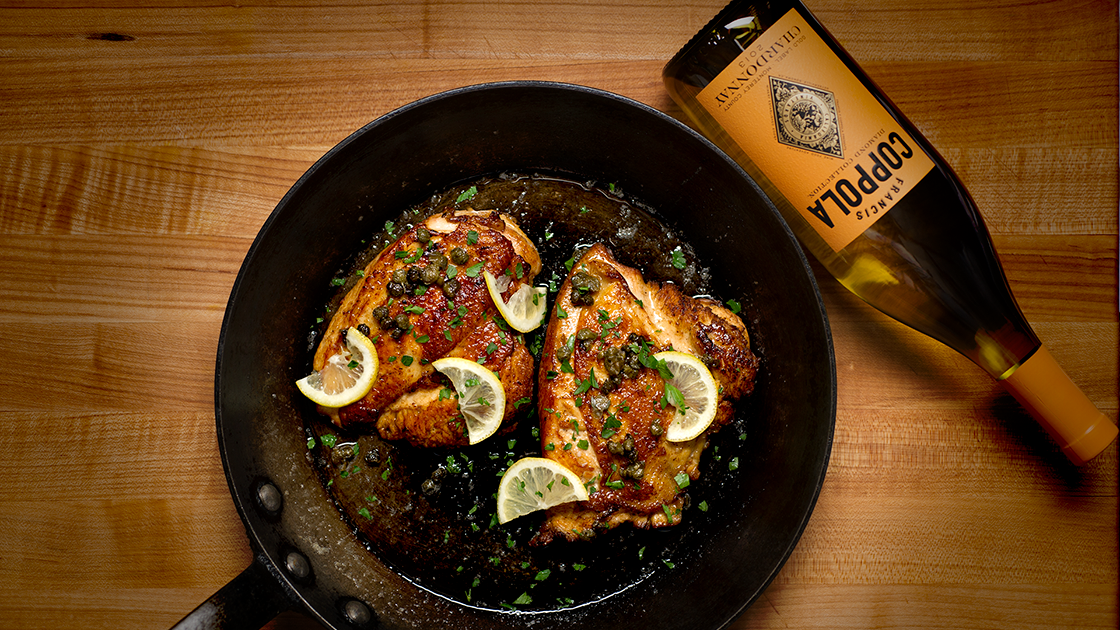 Chicken Piccata in a skillet and a bottle of chardonnay.
