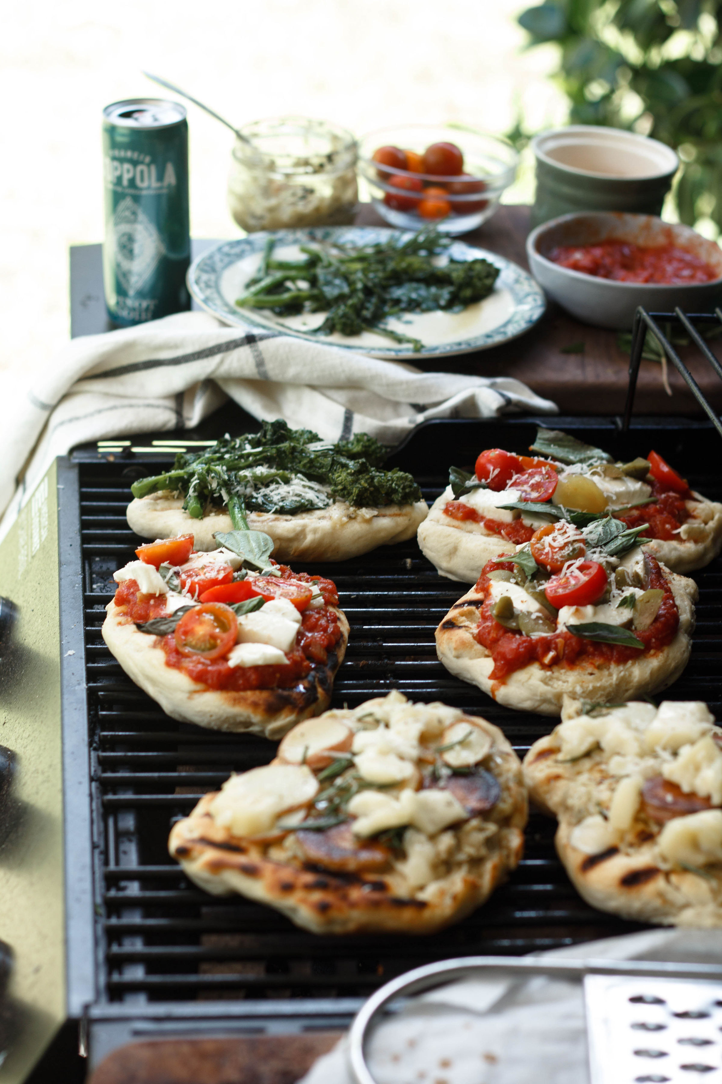 Small pizzas with toppings on a grill.