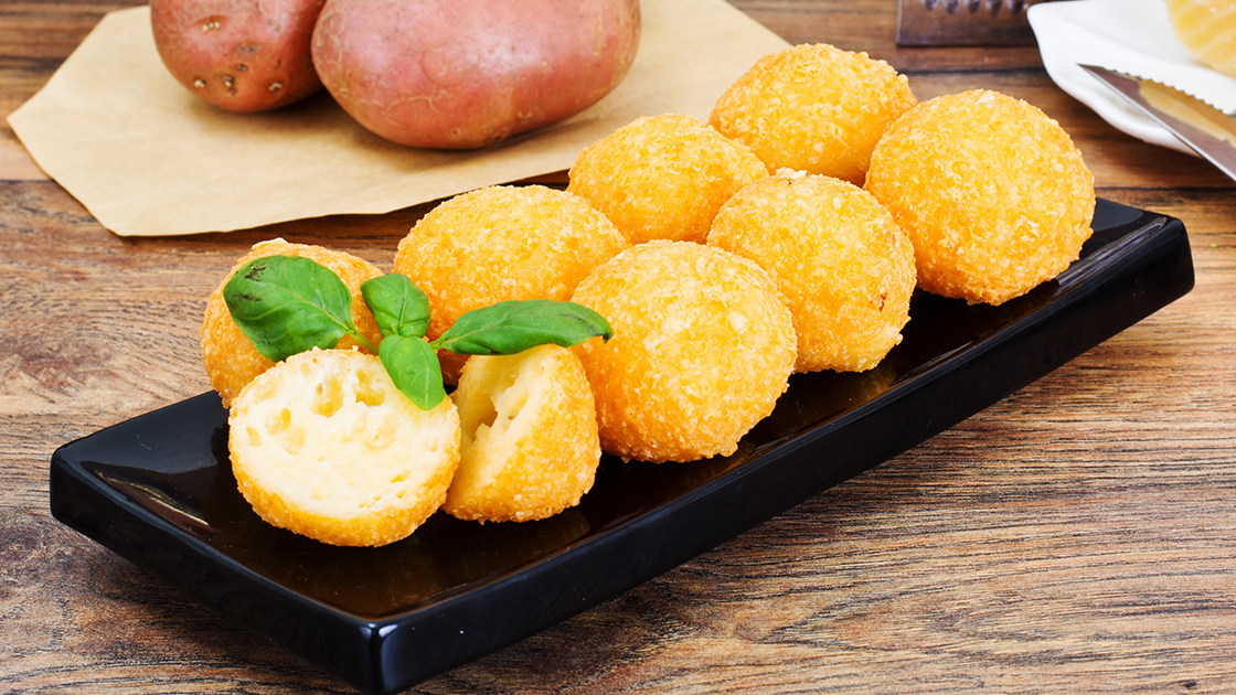 A plate with eight potato croquettes lined up on it.
