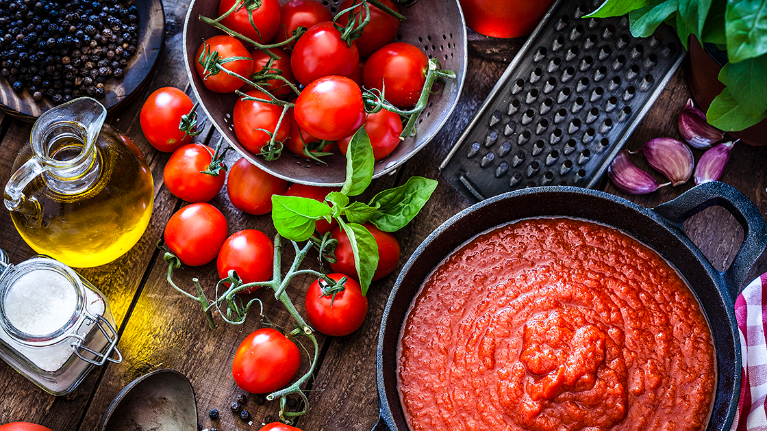 Pot of tomato sauce on a table next to a cheese grater, tomatoes on the vine and olive oil.