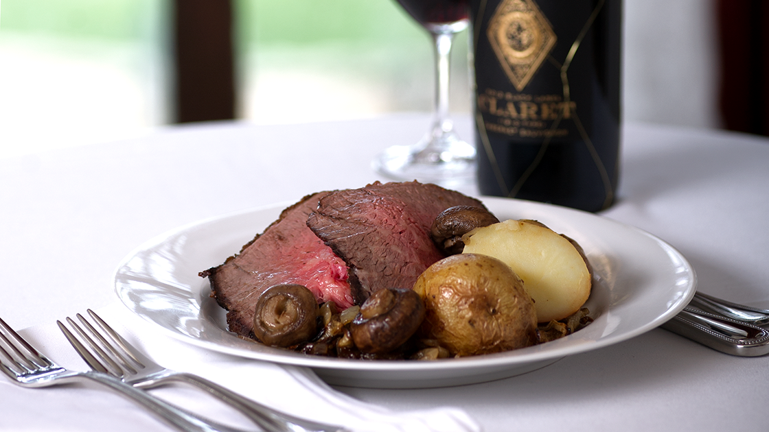 Roast on a plate with a bottle of Claret.
