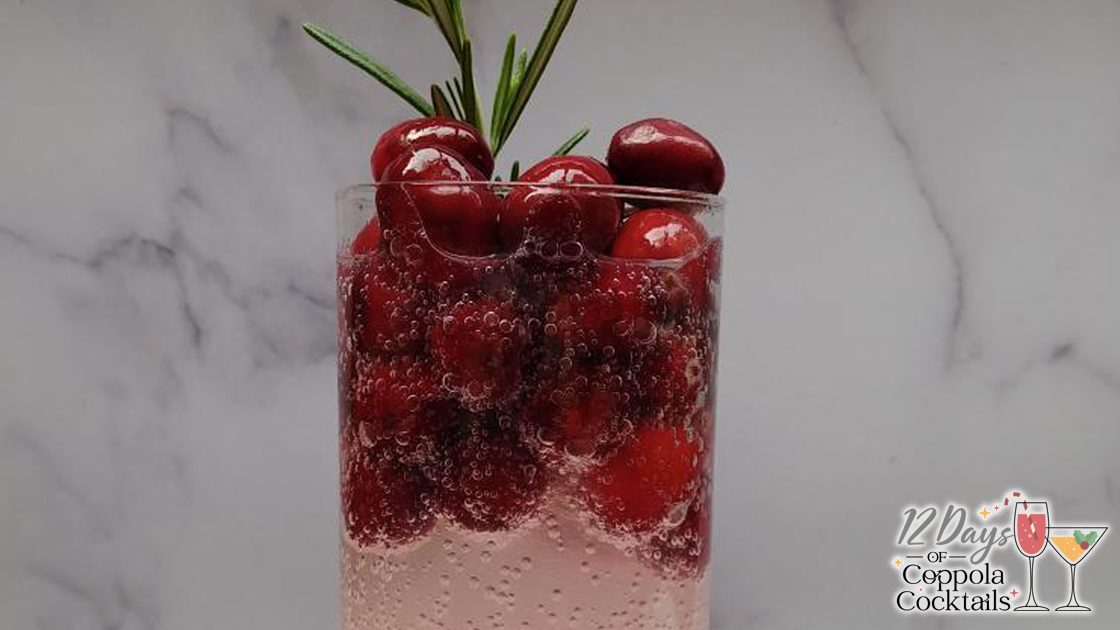 Close up of a cocktail garnished with cranberries and a sprig of rosemary.
