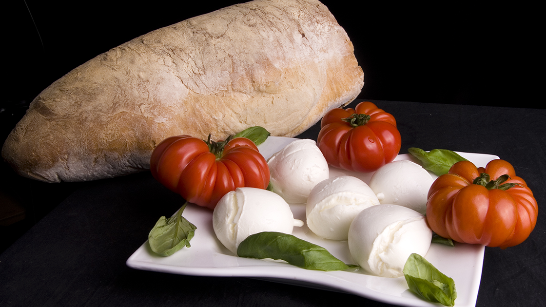 Large loaf of rustic bread with a plate of tomatoes, basil and mozzarella balls.