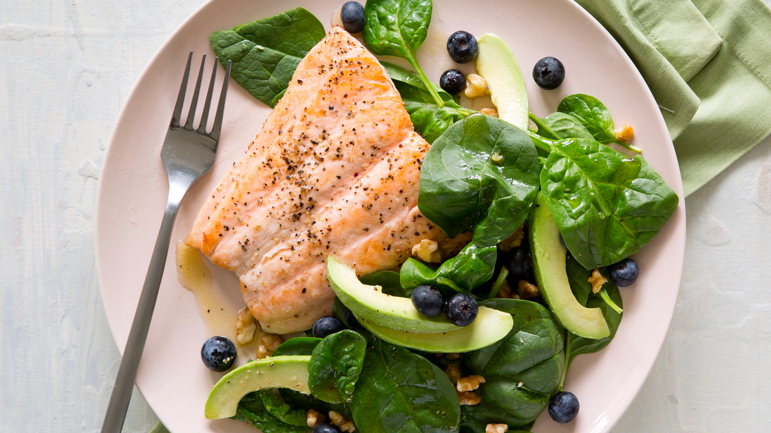 A plate with a large salmon fillet and spinach, avocado and blueberry salad.