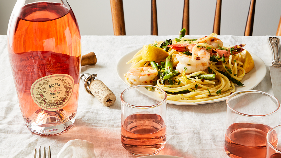 Sofia Rosé on a table with a shrimp pasta dish.