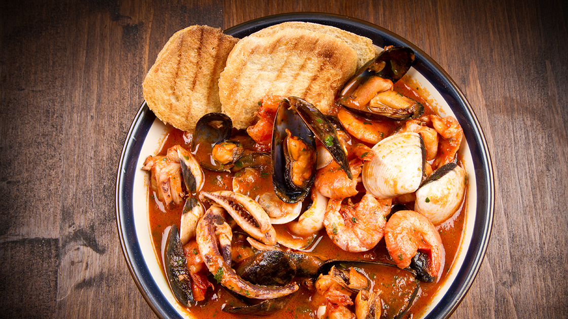 A large bowl of seafood stew garnished with toasted bread.