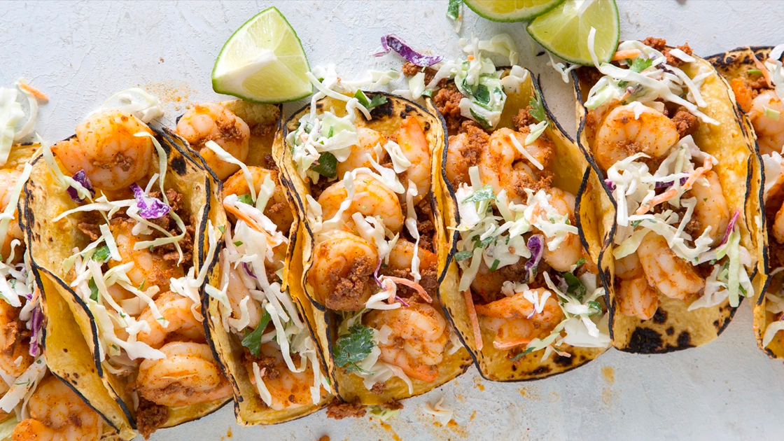 A row of shrimp tacos with lime wedges.