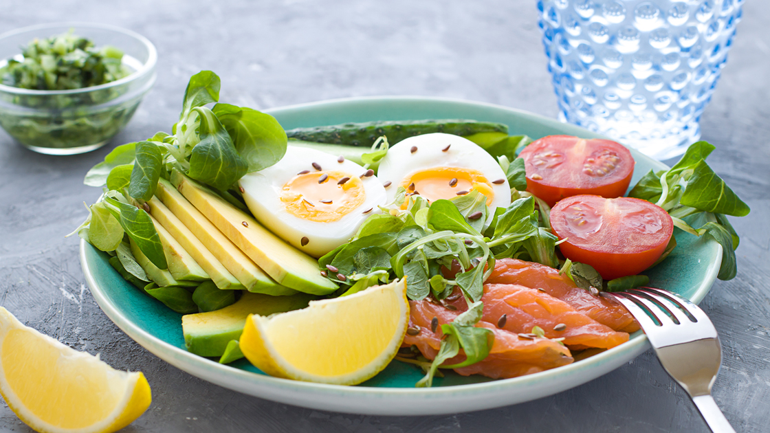 A healthy lunch plate featuring sliced avocado, hard-boiled egg, tomatoes, and smoked salmon.