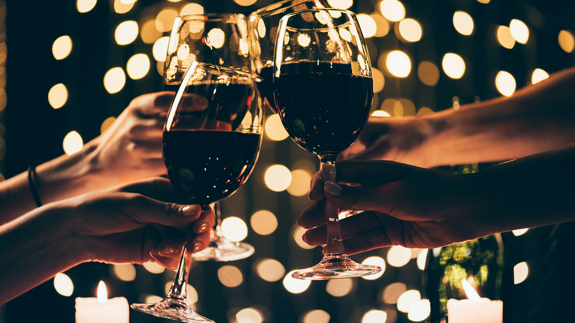 Four hands toasting with glasses of red wine with string lights in the background.