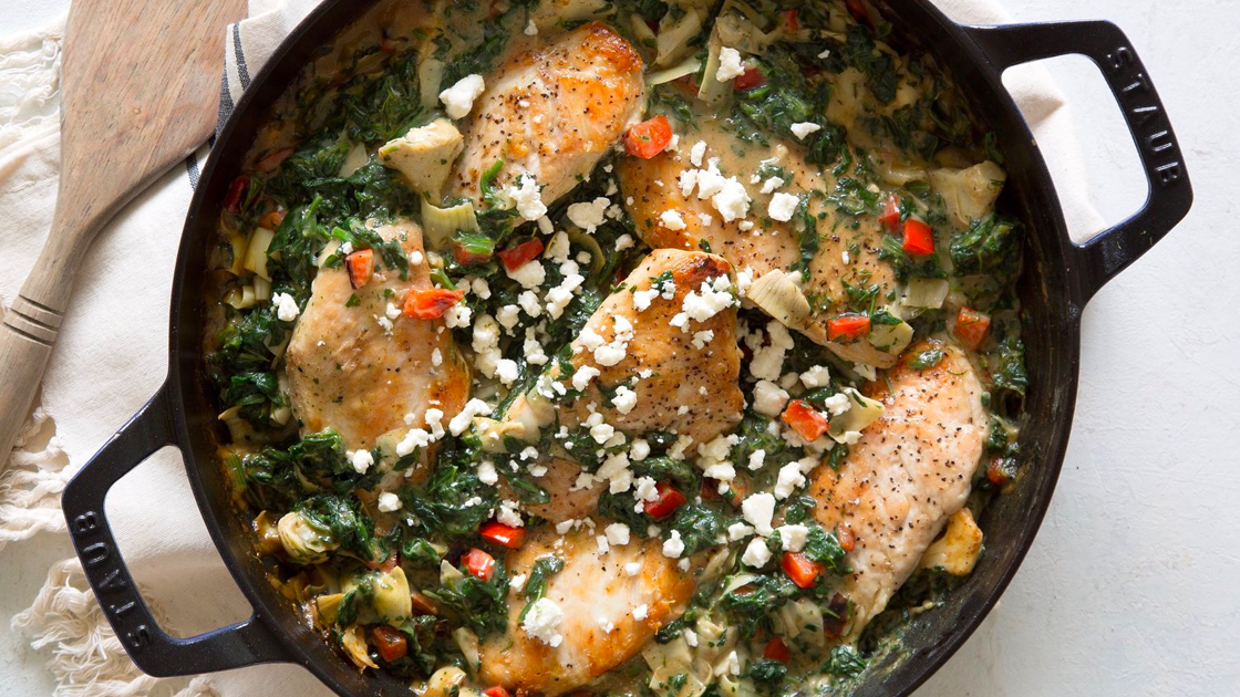 Cast Iron Skillet filled with spinach-artichoke chicken topped with feta cheese.