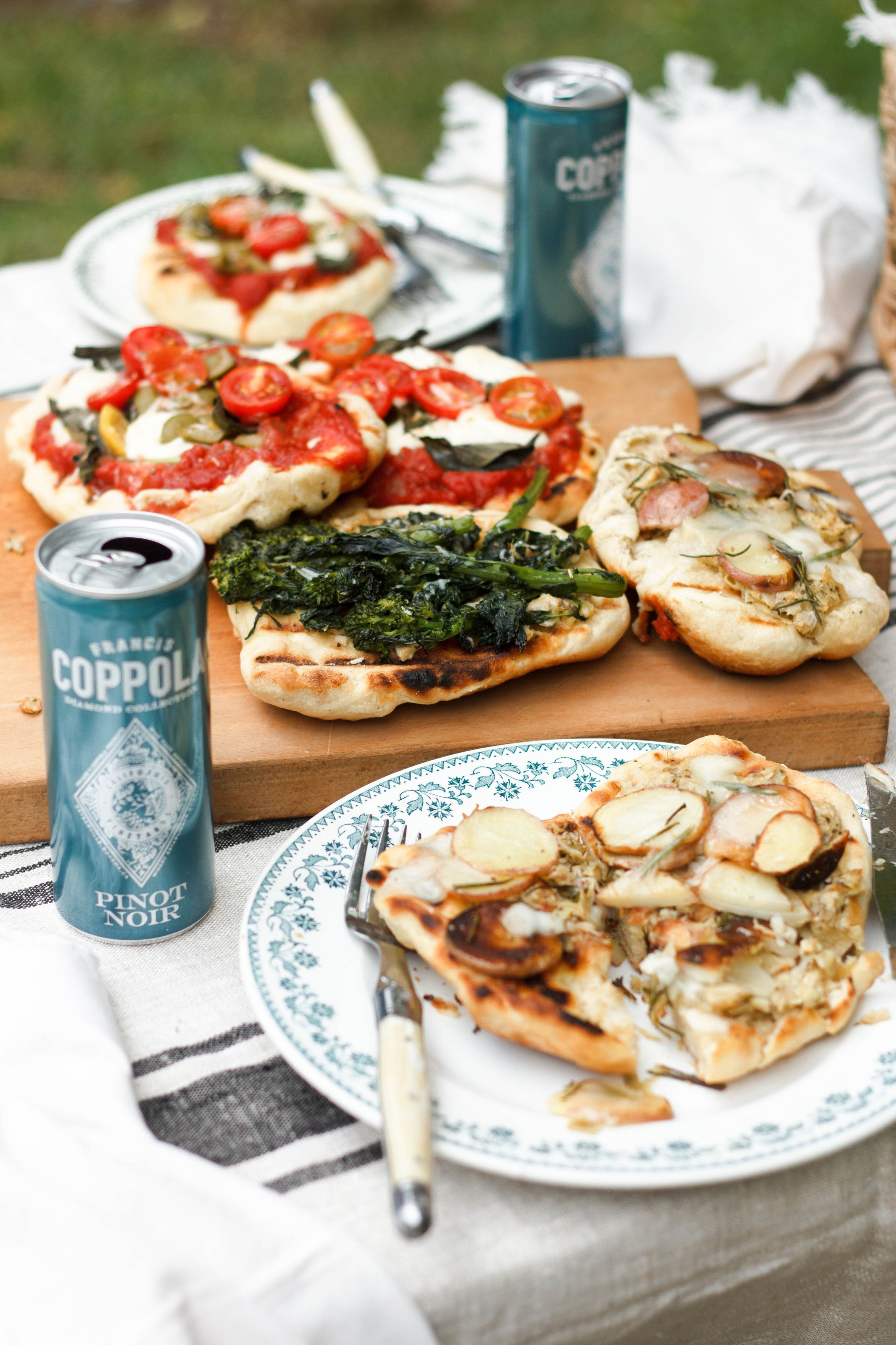 A table with an assortment of grilled pizzas and cans of pinot noir.