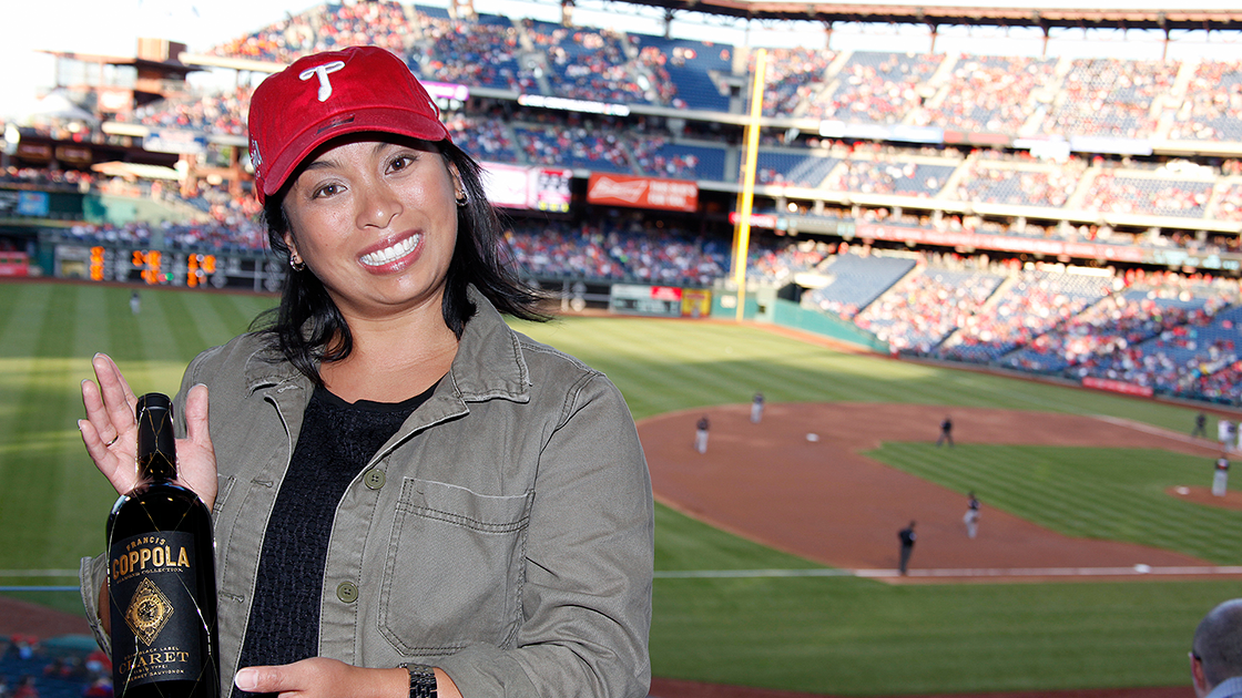 Woman in red baseball hat smiling holding a bottle of Claret with baseball stadium in background.