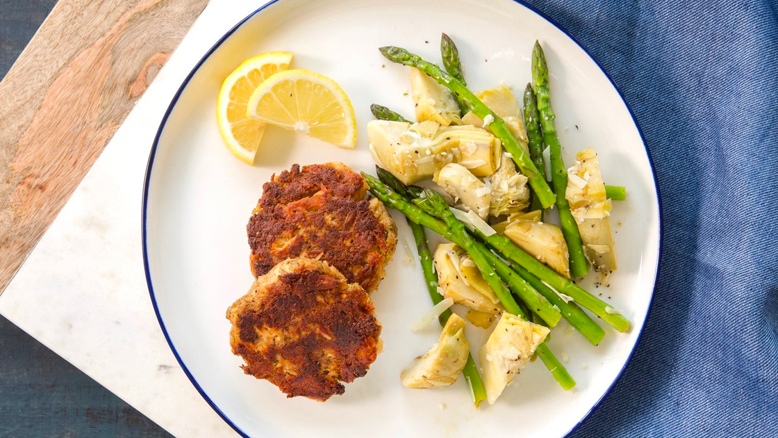 A plate with tune cakes, lemon wedges and a artichoke hearts and asparagus melody.