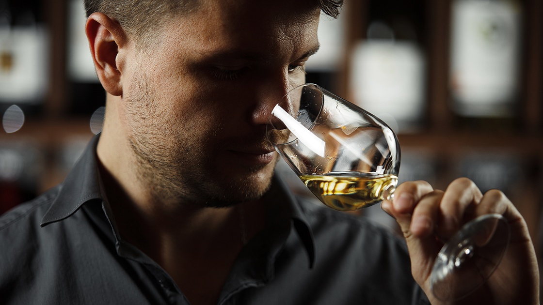 A man sniffing a glass of white wine.