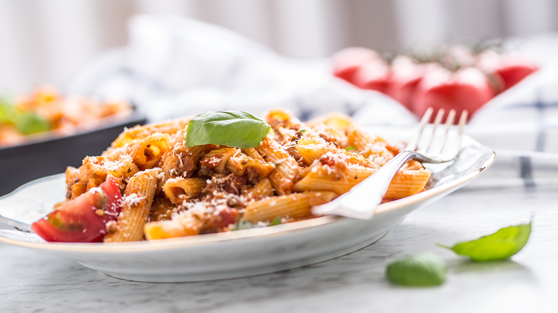 A dish piled high with rigatoni and meat sauce.