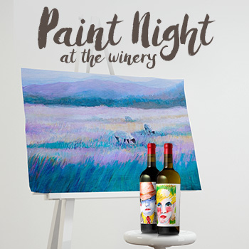 Two bottles of wine in front of a canvas on an easel with a painting of sheep in a field.