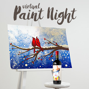 Painting of two cardinals on a snowy tree branch on an easel next to a bottle of wine.