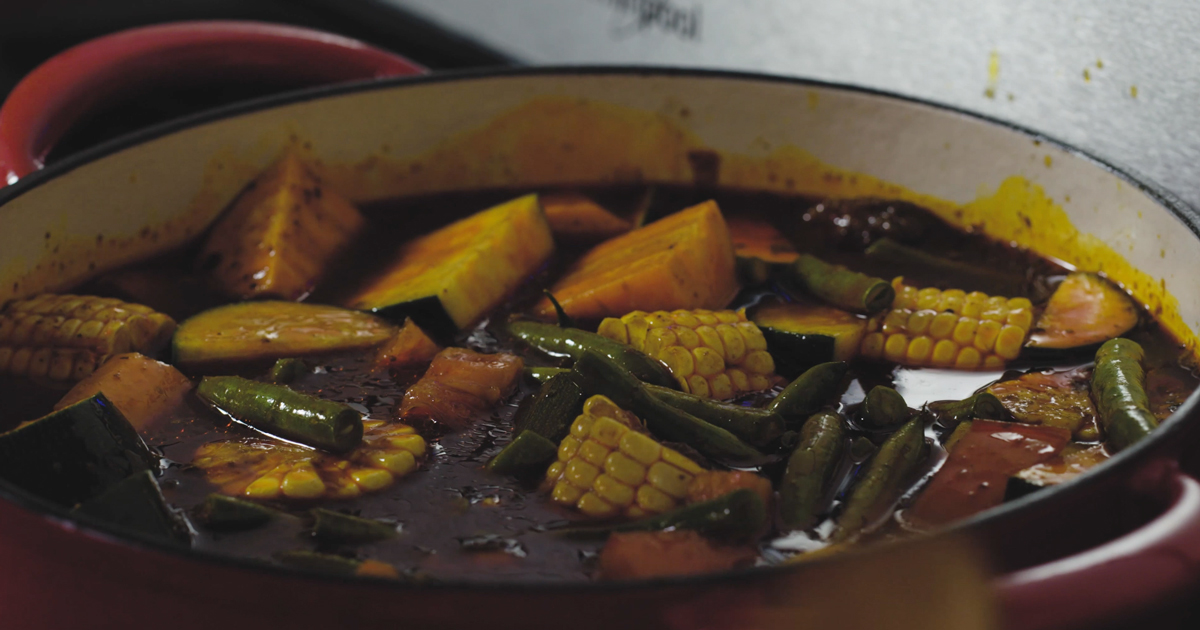 Caldo De Res stew cooking in a enameled cast iron pot.