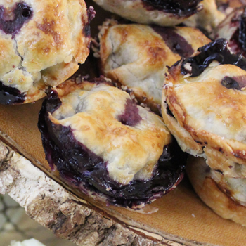 A stack of small blueberry pies.