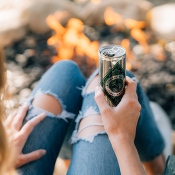 Woman's knees by a campfire holding a can of Diamond Collection wine.