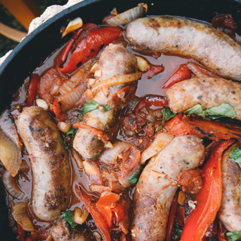 Close up of sausages and red peppers cooking in a cast iron skillet.