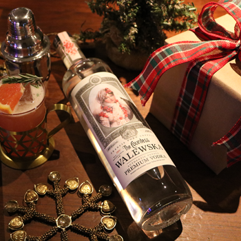 A bottle of Countess Walewska vodka laying down next to a wrapped gift box, a cocktail shaker and a garnished glass of the Blood Orange Sparkler cocktail.