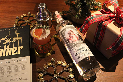 A bottle of Countess Walewska vodka laying down next to a wrapped gift box, a book about the Godfather film, a cocktail shaker and a garnished glass of the Blood Orange Sparkler cocktail.